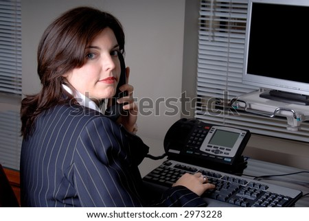 Young Businesswoman Sat At Her Office Desk Speaking On The Phone