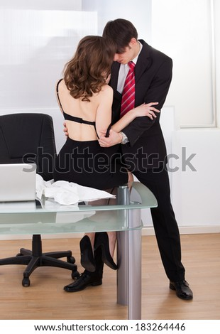 Young businesswoman seducing her boss in the office - stock photo