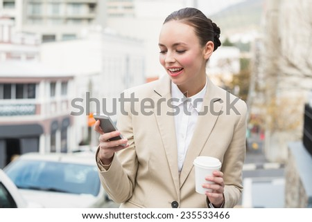 Young businesswoman sending a text outside in the city - stock photo