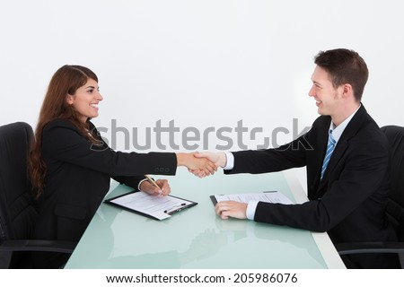 Young businesswoman shaking hand of male candidate during job interview - stock photo