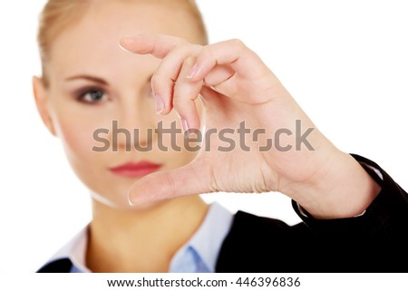 Young businesswoman showing copy space or something between fingers - stock photo