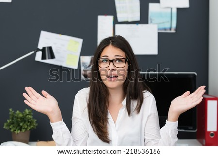 Young businesswoman showing her ignorance at the office shrugging her shoulders with a look of frustration - stock photo
