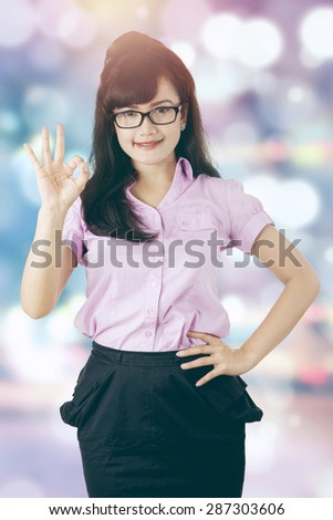 Young businesswoman showing okay sign, shot with light glitter background - stock photo