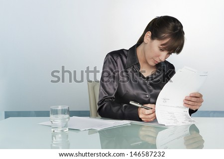 Young businesswoman signing contract at conference table - stock photo