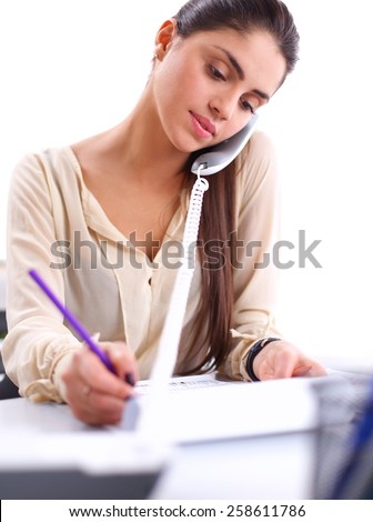 Young businesswoman sitting and talking on phone - stock photo