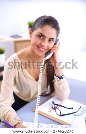 Young businesswoman sitting and talking on phone. - stock photo