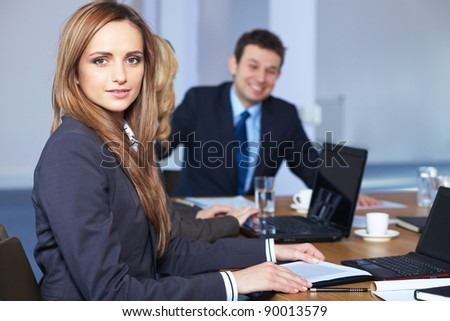 Young businesswoman sitting at conference table during business meeting - stock photo