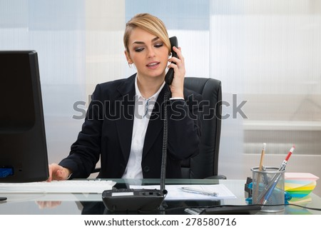 Young Businesswoman Sitting At Desk And Talking On Telephone In Office