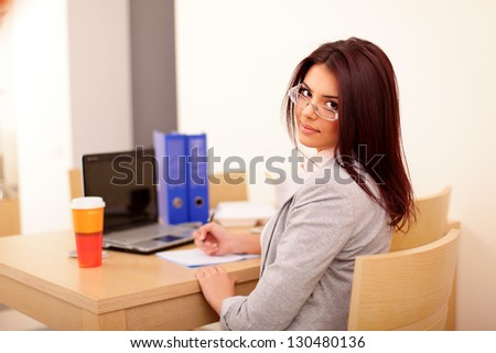 Young businesswoman sitting at desk and working. Smiling and looking back at camera - stock photo