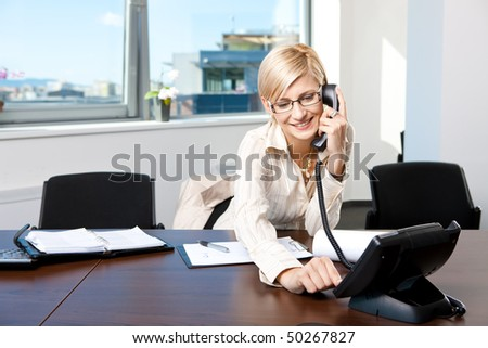 Young businesswoman sitting at desk in office, talking on landline phone, smiling. - stock photo