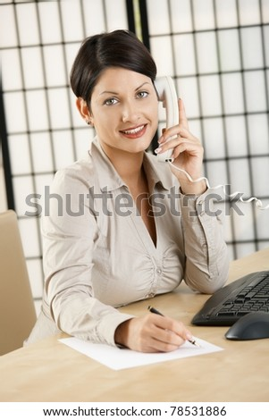 Young businesswoman sitting at desk in office, talking on phone, writing notes, smiling.? - stock photo