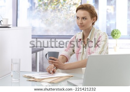 Young businesswoman sitting at desk in office, working, drinking tea. - stock photo