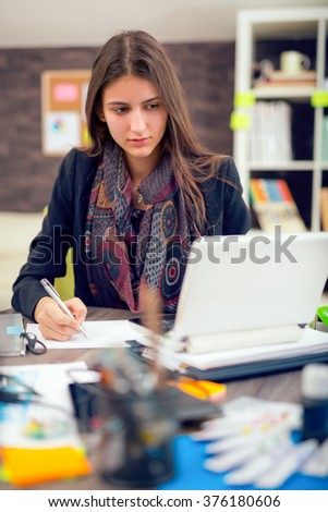 Young businesswoman  sitting at her desk in the office doing paperwork - stock photo