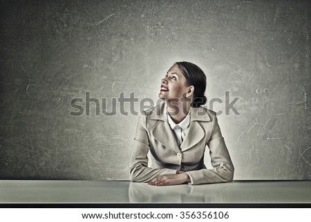 Young businesswoman sitting at table and looking away
