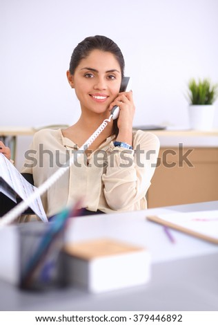Young businesswoman sitting at the desk and talking on phone - stock photo