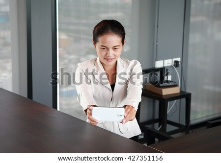 Young businesswoman sitting at the table on workplace in office using the smartphone taking pictures of herself