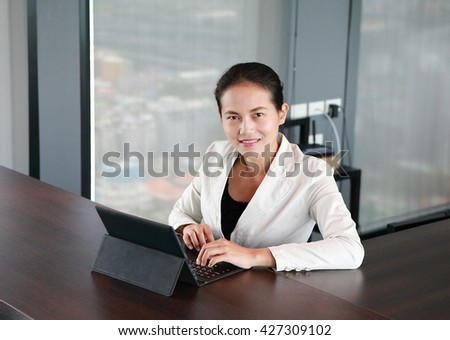 Young businesswoman sitting at the table on workplace in office with laptop computer