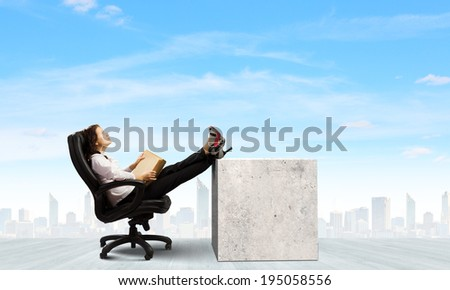 Young businesswoman sitting in chair and reading book