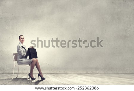 Young businesswoman sitting in chair with suitcase in hands