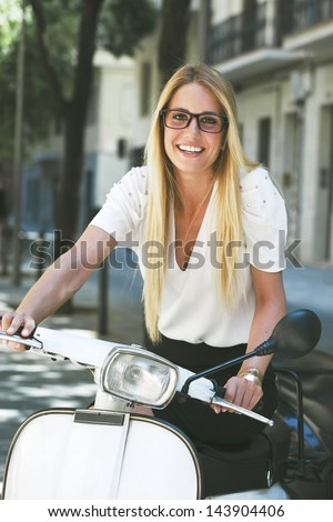 Young businesswoman sitting on a italian scooter. / Blonde woman standing on the street. - stock photo