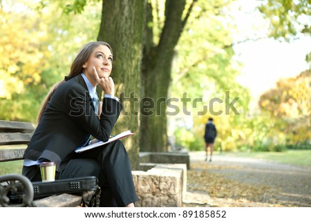 young businesswoman  sitting on bench in park and thinking, outdoor - stock photo