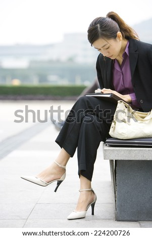 Young businesswoman sitting on bench looking down at cell phone - stock photo