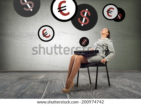 Young businesswoman sitting on chair and looking at currency symbols above - stock photo