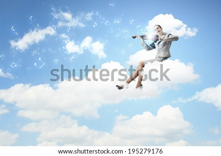 Young businesswoman sitting on cloud and playing violin