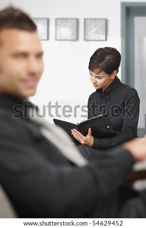 Young businesswoman sitting on sofa at office anteroom looking at organizer waiting. - stock photo