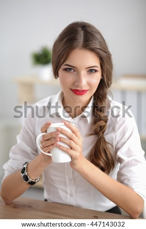 Young businesswoman sitting on the desk with with cup - stock photo