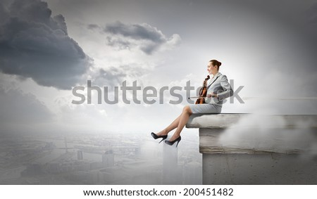 Young businesswoman sitting on top of building and playing violin