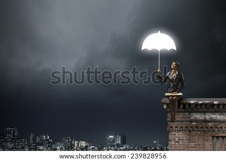 Young businesswoman sitting on top of building with book