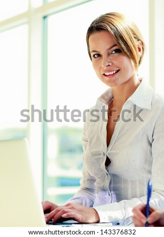Young businesswoman sitting with laptop