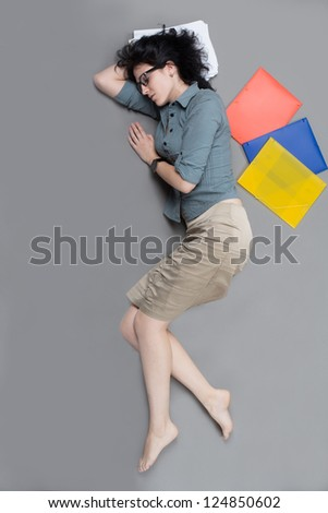 Young businesswoman sleeping on the floor in her office - stock photo