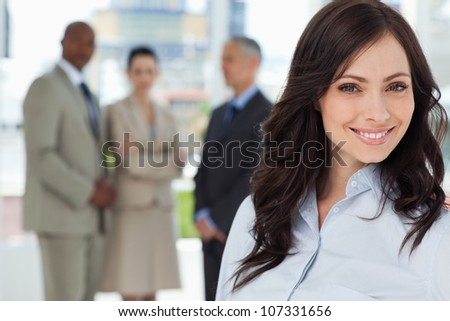 Young businesswoman smiling and looking ahead with the team in the background