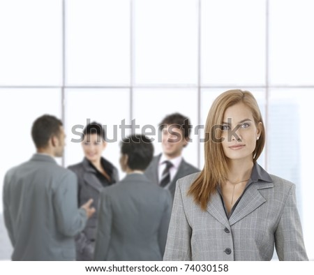 Young businesswoman smiling at camera with team talking in background.? - stock photo