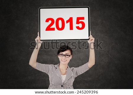 Young businesswoman smiling at the camera while holding a whiteboard with number 2015 - stock photo