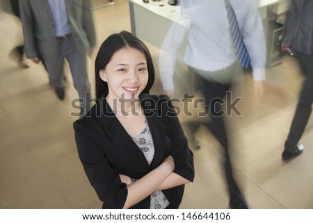 Young businesswoman smiling in the office, businessmen walking all around her - stock photo