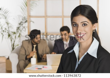 Young businesswoman smiling with her colleagues in the background