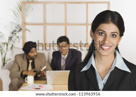 Young businesswoman smiling with her colleagues in the background - stock photo