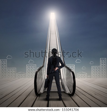 Young businesswoman standing at escalator with cityscape - stock photo
