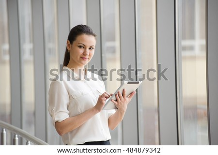 young businesswoman standing by window in office beautiful young female model in bright office beautiful bright office