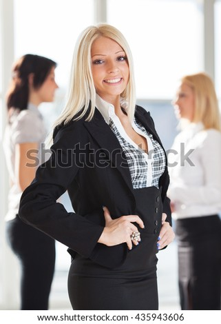 Young businesswoman standing in front of her associates.