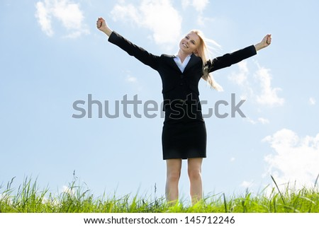 Young Businesswoman Standing In Grass With Arm Extended - stock photo