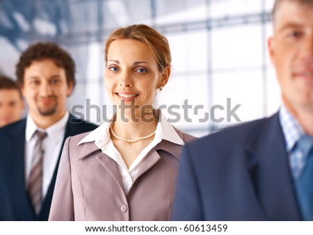 Young businesswoman standing in the row of the business people. - stock photo