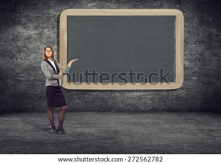 Young businesswoman standing near a blank board pointing at her.