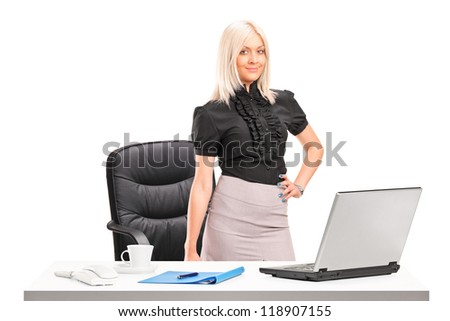 Young businesswoman standing next to desk with laptop isolated on white background