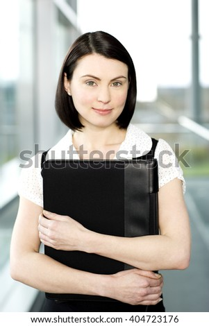 Young businesswoman standing on office walkway holding folder of papers - stock photo