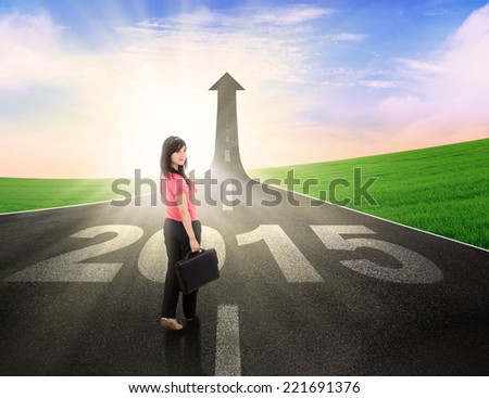 Young businesswoman standing on the road with number 2015 and upward arrow