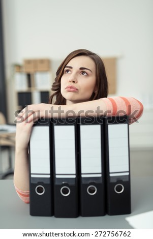 Young businesswoman standing thinking resting her arm across a row of office binders with blank labels as the stares in to the air with a contemplative expression - stock photo